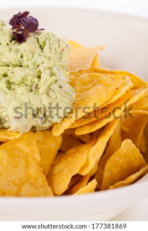 Crisp corn nachos with spicy fresh guacamole sauce and a topping of avocado served as a snack or appetizer in a white bowl - stock photo