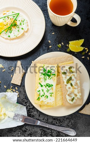 Crisp Crispbread with curd cheese spread with chives and seeds, fried egg and morning tea - stock photo