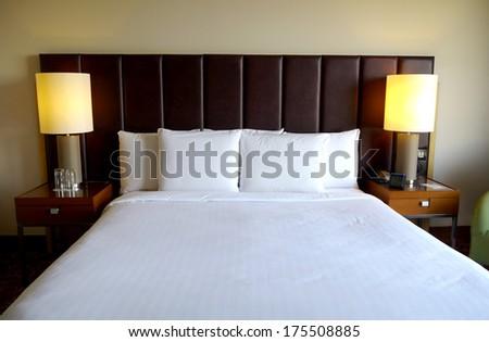 crisp white bed in hotel room - stock photo