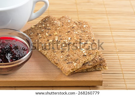 Crispbread fragment of white cup and jam in a vase. - stock photo