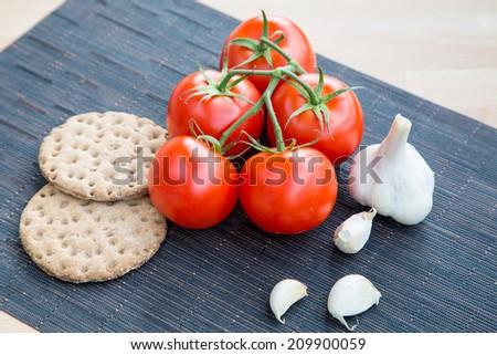 Crisps, garlic and tomatoes - stock photo