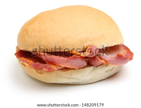 Crispy bacon in a soft white bread roll or bap. - stock photo
