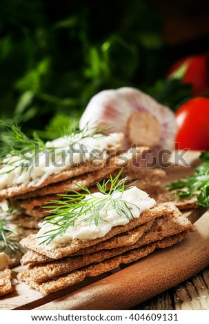 Crispy bread with soft cheese and herbs, selective focus - stock photo