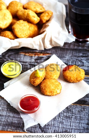 Crispy breaded golden chicken nuggets on parchment paper.  Ketchup and mustard near it. Textured wood background, Bowl with nuggets and glass of cola on backside - stock photo