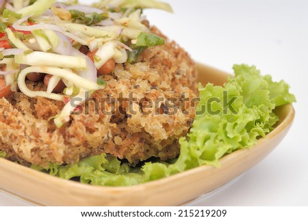 Crispy catfish spicy salad with green mango, Thai food,Crispy catfish salad with green mango and vegetable , served with tomato and lettuce