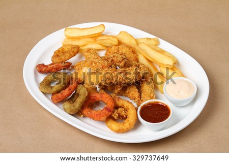 crispy chicken breasts, onion rings, baked potato - American food - fast food - stock photo