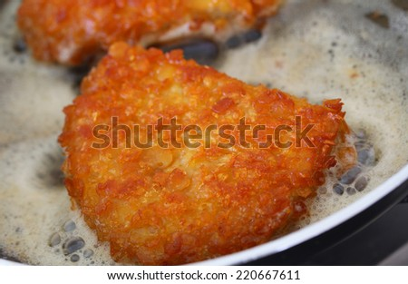 Crispy chicken fillet in the frying pan, closeup  - stock photo
