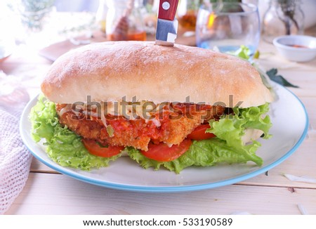 Crispy coated fried chicken in fresh baguette closeup filled with mozzarella cheese.