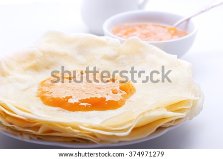 Crispy crepes with apricot jam - stock photo