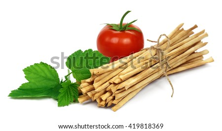 Crispy crunchy long bread sticks with tomato and green leaf, isolated on a white background. - stock photo