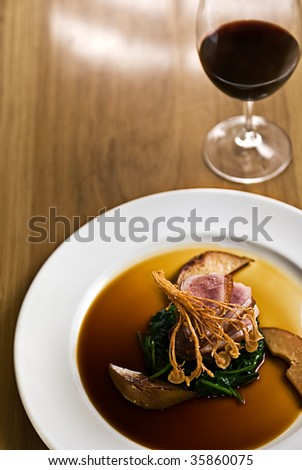 Crispy duck on a bed of spinach served with red wine in a restaurant. - stock photo