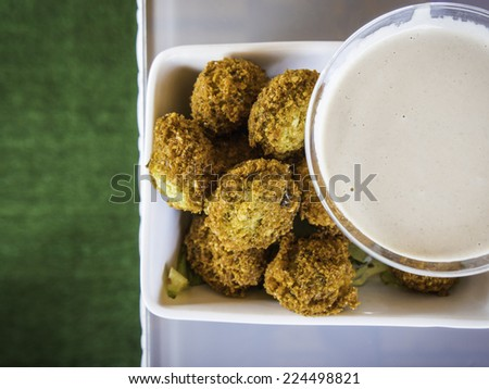 Crispy Falafels in a white bowl with a cup of tahini sauce - down view - stock photo