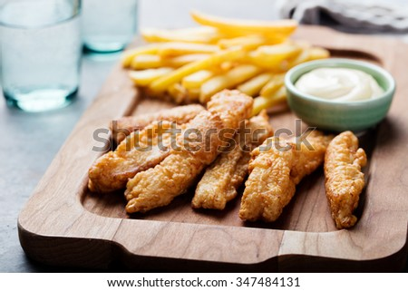 Crispy Fish and Chips with Tartar Sauce Traditional British food on a wooden board - stock photo