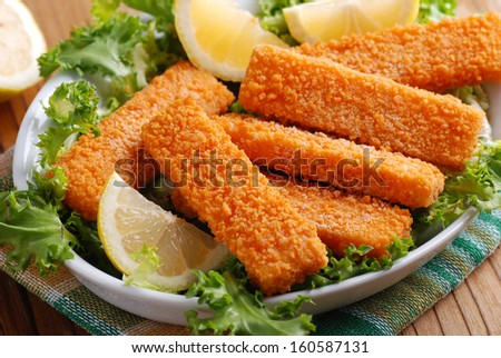 crispy fish sticks with vegetables and lemon slices