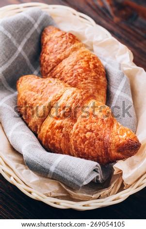 Crispy fresh croissants in a basket on dark wooden background - stock photo