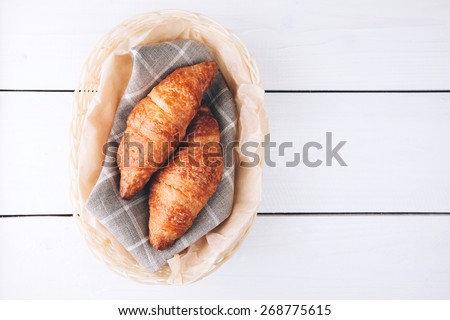 Crispy fresh croissants in a basket on white wooden background - stock photo