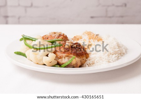 crispy fried chicken thighs with vegetables over rice in a lemon sauce - stock photo