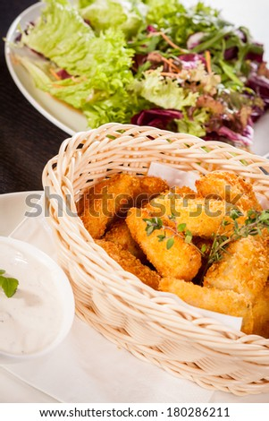 Crispy fried crumbed chicken nuggets in a wicker basket served as a finger food or appetizer with a creamy dip in a bowl alongside - stock photo