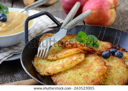 Crispy fried homemade potato pancakes served in an iron pan with apple sauce - stock photo