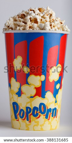 crispy fried popcorn in big striped box on a gray background - stock photo