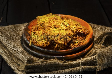 crispy fried potato fritter on an old clay plate and wood as ckground - stock photo