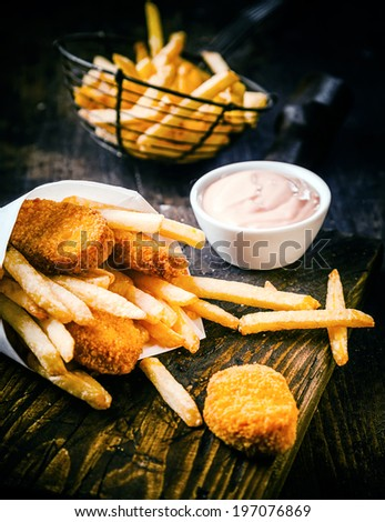 Crispy golden deep fried fish and potato chips, or French fries, served with a savory mayonnaise dip on an old wooden table in a fish shop - stock photo