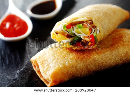 Crispy golden fried vegetable spring rolls with fresh ingredients served with soy and sweet and sour sauce in an oriental restaurant - stock photo