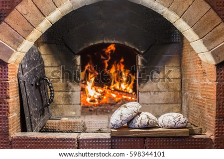 Crispy loaf of bread lying on the edge of the Russian stove on the hearth