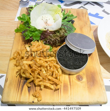 Crispy noodle and caviar with Soft-boiled egg with salad - stock photo