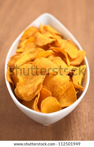 Crispy Peruvian sweet potato chips in white ceramic  bowl on wood (Selective Focus, Focus one third into the sweet potato chips) - stock photo