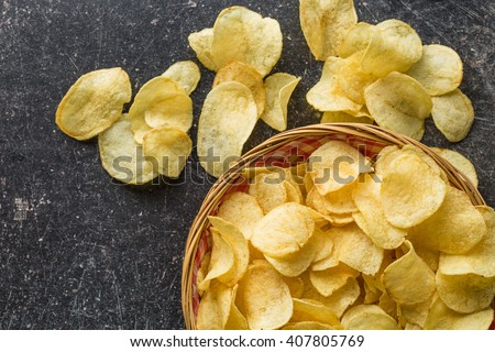 Crispy potato chips in a wicker bowl on old kitchen table - stock photo