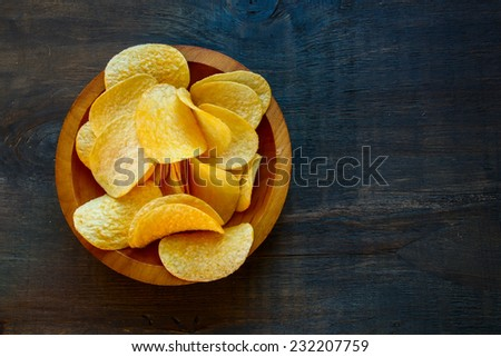 Crispy potato chips in bowl on wooden background, top view - stock photo
