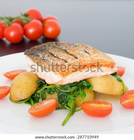 Crispy salmon with spinach, potatoes and tomatoes - stock photo