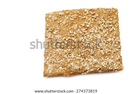 crispy spelt cracker with crushed wheat kernels on a white background - stock photo
