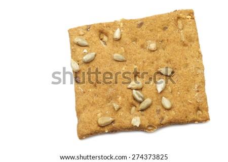 crispy spelt cracker with sunflower seeds on a white background - stock photo