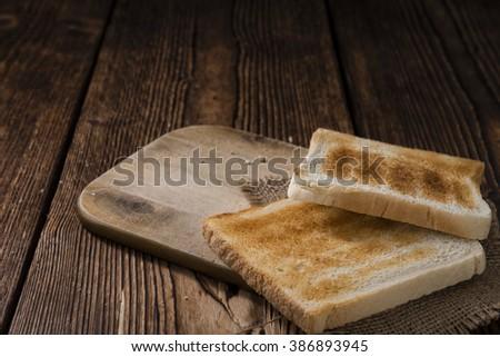 Crispy Toast Bread (selective focus) on wooden background - stock photo