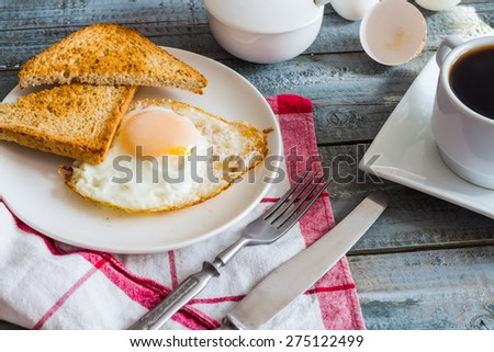 crispy toast with a fried egg and a cup of coffee. breakfast on the wooden background - stock photo
