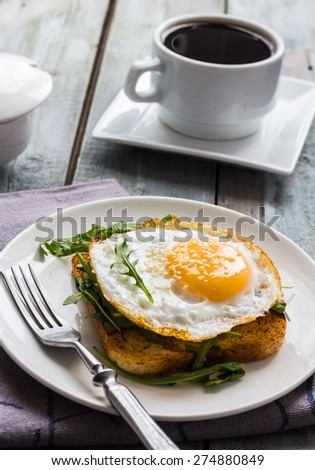 crispy toast with a fried egg and fresh arugula, a cup of coffee, breakfast on the wooden background - stock photo