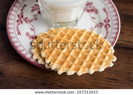 Crispy waffels on a dessert plate with a glass of fresh milk for breakfast or snack, selective focus - stock photo