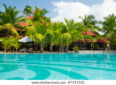 Cristal clear swimming pool surrounded by coconut palm trees - stock photo