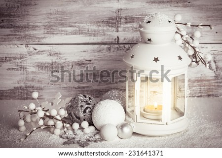 Cristmas lantern with decorations and snow over white shabby wooden background - stock photo