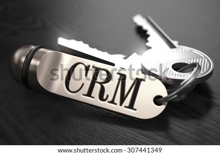 CRM - Customer Relationship Management - Concept. Keys with Keyring on Black Wooden Table. Closeup View, Selective Focus, 3D Render. Black and White Image. - stock photo