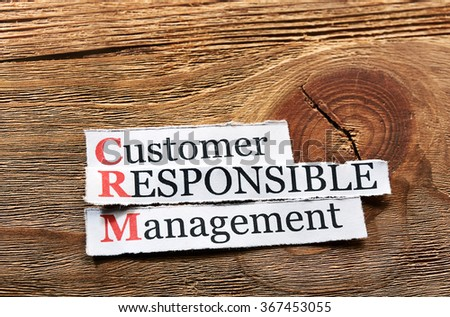 CRM - Customer Responsible Management written on paper on wood - stock photo
