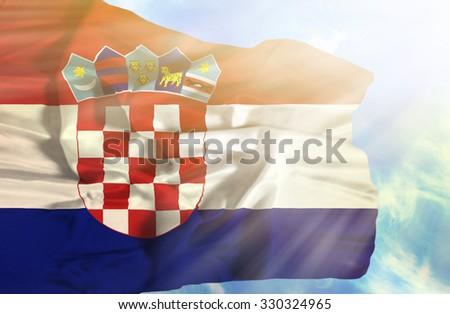 Croatia waving flag against blue sky with sunrays - stock photo