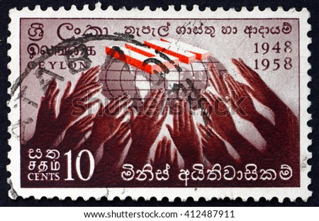 CROATIA ZAGREB, 28 MARCH 2016: a stamp printed in Sri Lanka shows Hands Reaching for UN Symbol, 10th Anniversary of the Signing of the Universal Declaration of Human Rights, circa 1958 - stock photo