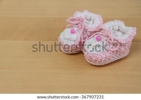 crochet baby booties  on wood - stock photo