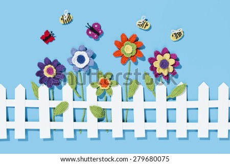 crochet flowers behind a white paper fence with bees and two butterflies on a blue background