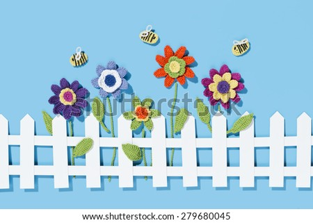crochet flowers behind a white paper fence with bees on a blue background