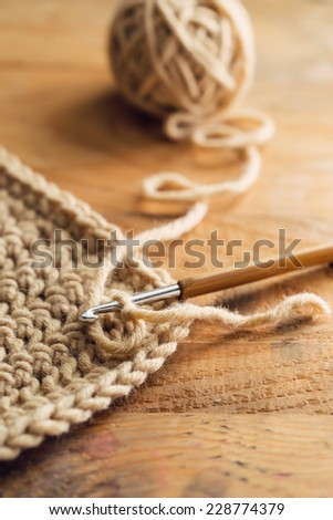 Crochet hook on wooden background - stock photo