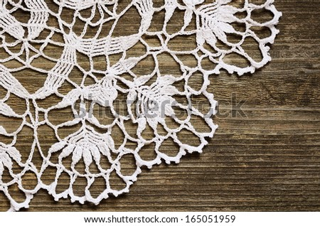 Crochet lace on an old weathered wood - stock photo